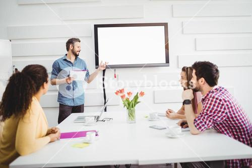 Colleagues listening to executive in meeting at creative office