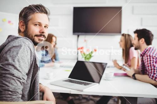 Portrait of confident executive in meeting at creative office