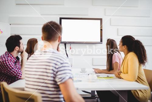 Executives watching at television during training in creative office