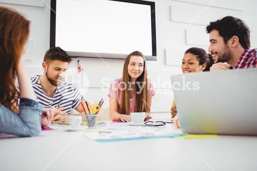 Happy coworkers discussing in meeting at creative office