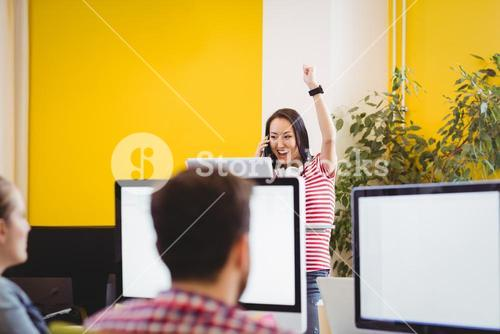 Graphic designer with raised arm in creative office