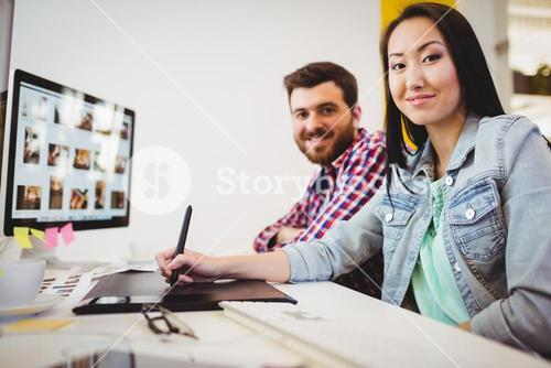 Smiling business people with graphic tablet at desk