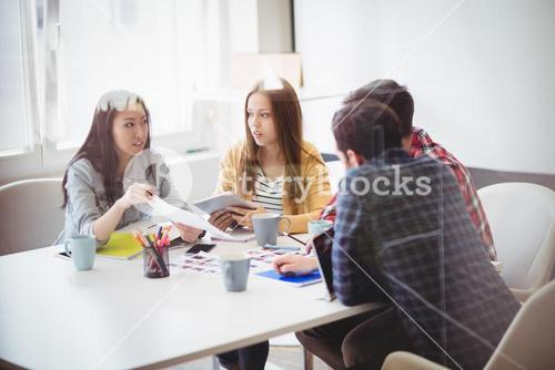 Editors discussing in meeting room