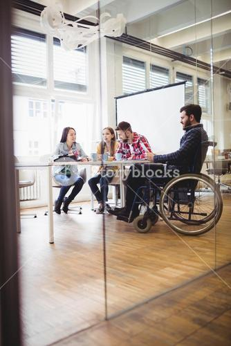 Businessman on wheelchair with photo editors in meeting room