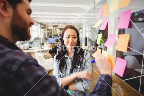 Female photo editor standing near male coworker writing on sticky note