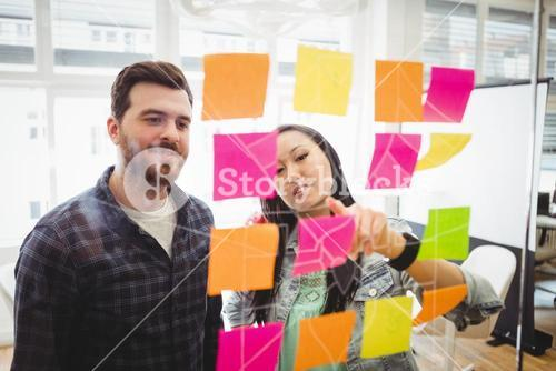 Business people looking at multi colored sticky notes on glass