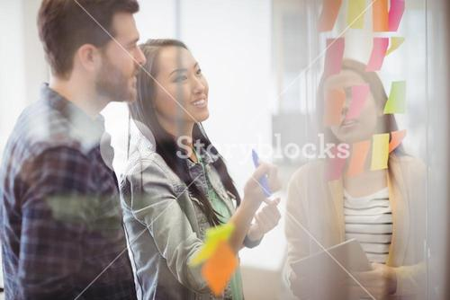 Female photo editor with coworker looking at multi colored sticky notes