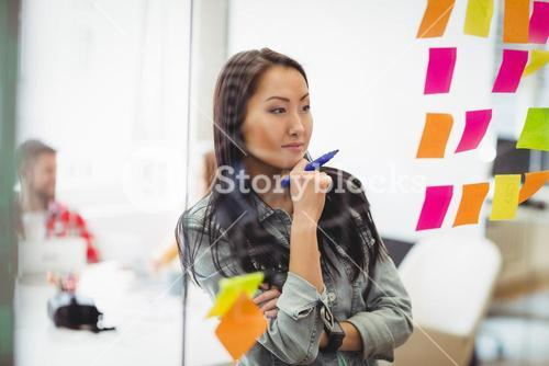 Female photo editor looking at multi colored sticky notes