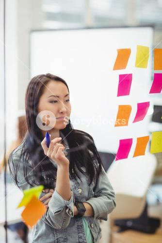 Creative businesswoman looking at multi colored sticky notes