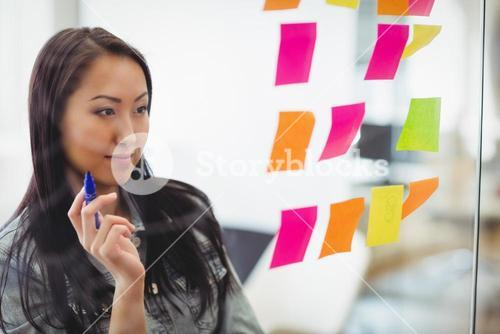 Confident creative businesswoman looking at multi colored sticky notes