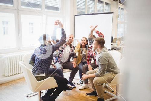Excited creative business people giving high-five