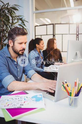 Creative business people using technologies at desk