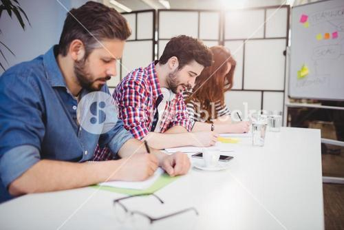Business people writing on documents in meeting room