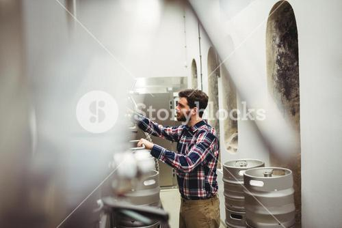Manufacturer inspecting machineries in brewery