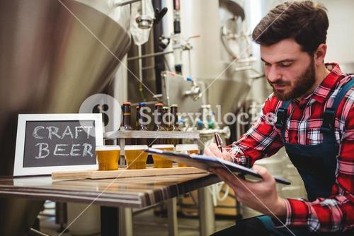 Manufacturer writing on writing pad in brewery