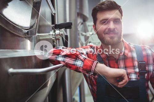 Confident manufacturer standing in brewery