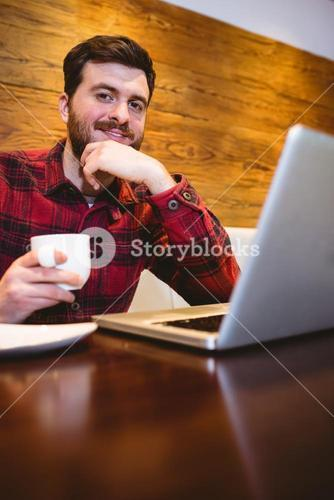 Man with laptop and coffee in restaurant