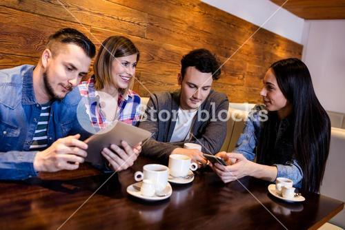 Friends using digital tablet and mobile phone at restaurant