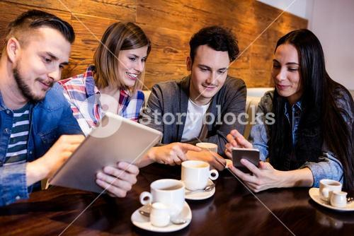 Friends with digital tablet and mobile phone at restaurant