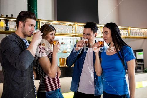 Friends drinking beer by bar counter