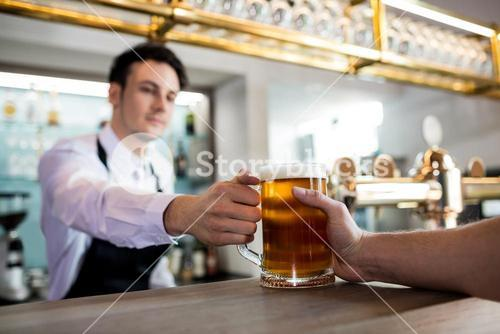 Barkeeper serving beer to customer