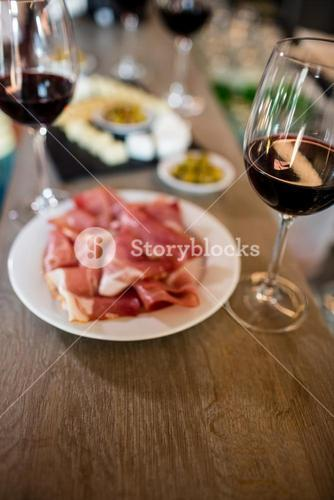 Meat and wineglass on table at bar