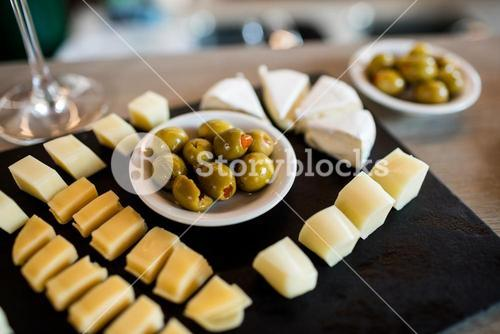 Cheese slices and olives on tray