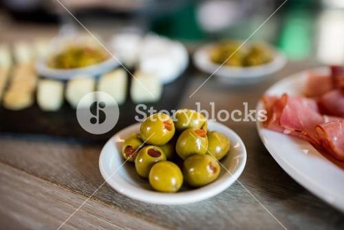 Green olives in bowl on table