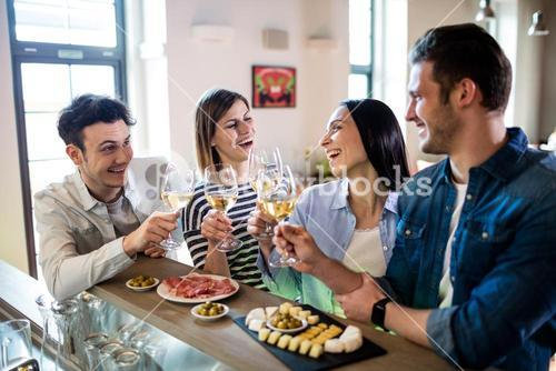 Young friends enjoying wine and food at counter