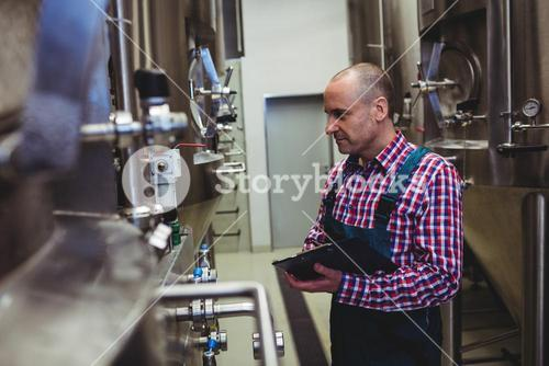 Manufacturer examining machinery at brewery