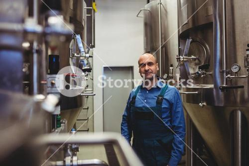 Confident owner standing amidst manufacturing equipment