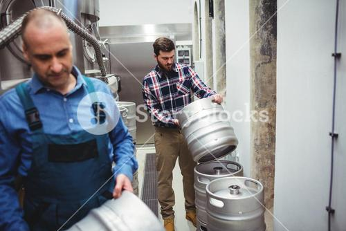 Manufacturer and worker carrying kegs