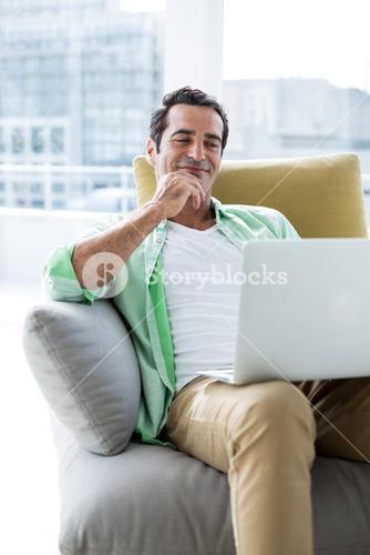 Man smiling while looking in laptop