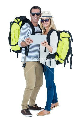 Cheerful couple with luggage and digital tablet