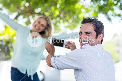 Happy man photographing woman