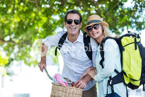 Cheerful couple with bicycle on street