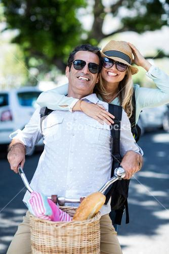 Couple riding bicycle on street