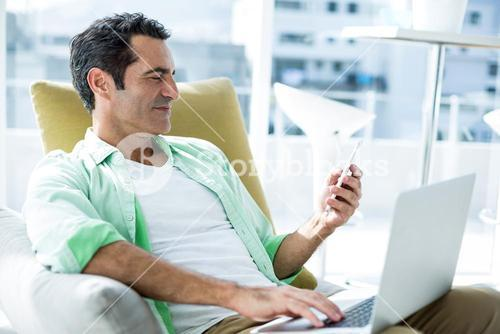 Man using cellphone on couch