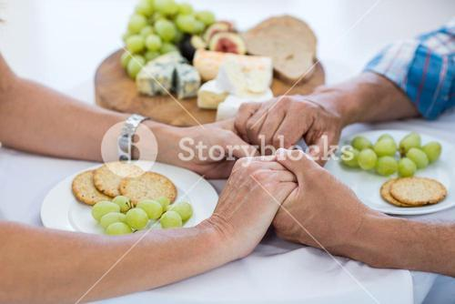 Couple holding hands while having food
