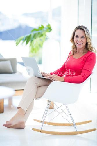 Woman using laptop on rocking chair
