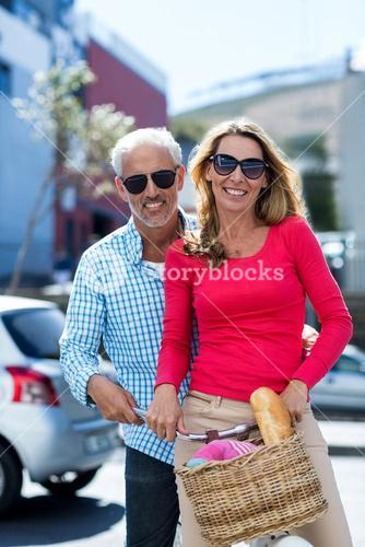 Mature couple riding bicycle on city street