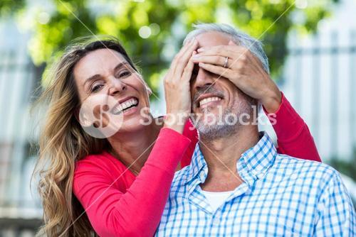 Mature woman covering eyes of man