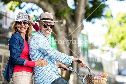 Portrait of mature couple riding bicycle