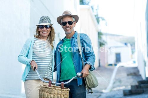Mature couple with bicycle standing in city