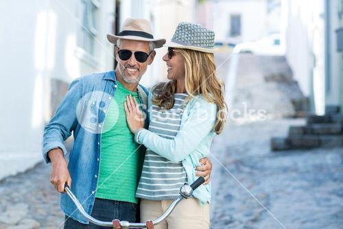Mature couple with bicycle on street