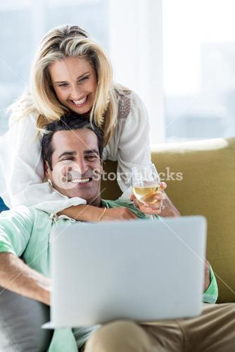 Romantic couple using laptop at home