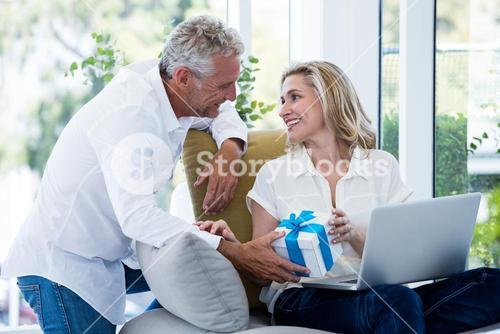 Happy man giving gift to woman with laptop