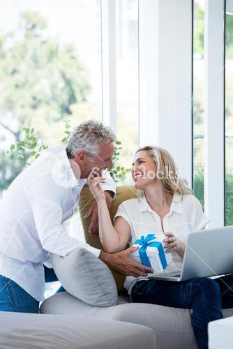 Romantic couple with gift and laptop
