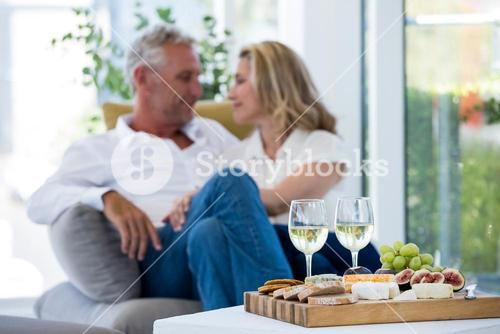 White wine and food on table with romantic couple