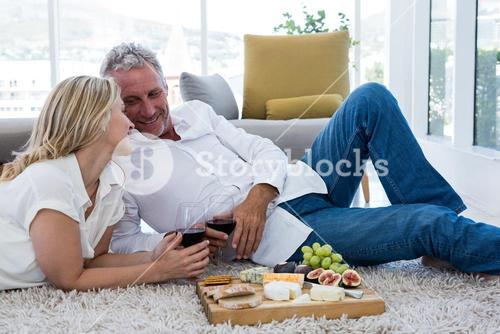Romantic couple with red wine and food while lying on rug